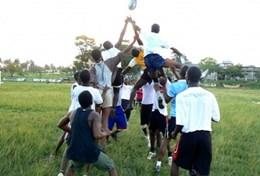 Sports players catch the ball during a line-out in a rugby match at our volunteer Rugby placement in Ghana.
