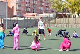 A volunteer works with a group of children on their fitness during a school sports lesson in Mongolia.