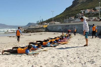 Disadvantaged children stretch alongside Surfing volunteers in Cape Town