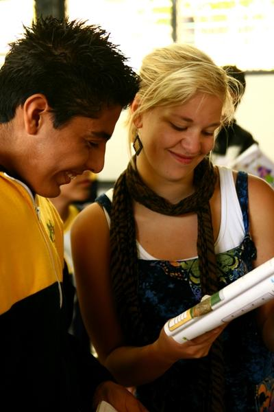 A volunteer on the Teaching project in Mexico and a local student smile while looking at a book