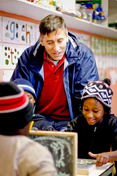A Projects Abroad volunteer helps learners with their work at a local school