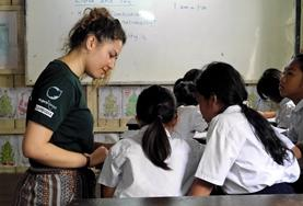A Teaching volunteer explains an English activity to school children during a lesson in Cambodia.