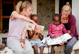 Teaching volunteers read English books with local children in Tanzania to improve their literacy skills.