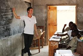 A Teaching volunteer demonstrates a lesson on a blackboard to a class of school students in Togo.