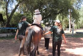 Equine Therapy volunteers assist a disabled child as he rides his therapy horse during treatment in Bolivia.